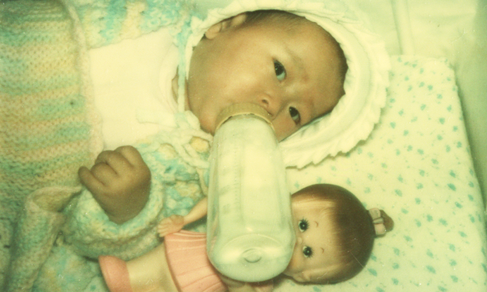 JS LEE as an infant with white doll-Credit Unknown
